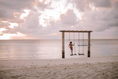 Woman on a swing at the sea at sunset, Maguhdhuvaa Island, Gaafu Dhaalu Atoll, Maldives - DAWF01227