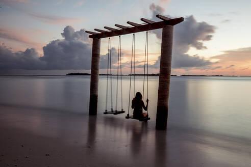 Woman on a swing at the sea at sunset, Maguhdhuvaa Island, Gaafu Dhaalu Atoll, Maldives - DAWF01257