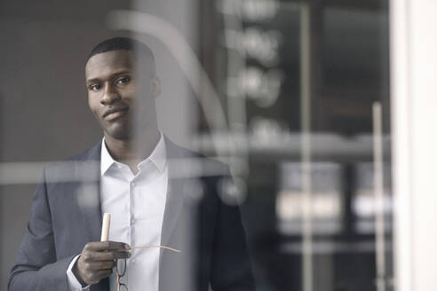 Portrait of smiling young businessman behind diagram on glass pane in office - KNSF07417