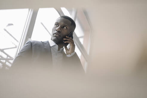 Portrait of young businessman in front of window on the phone - KNSF07423