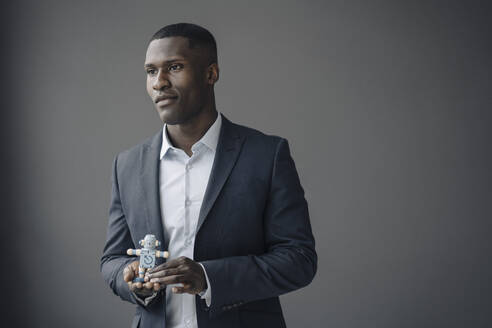 Portrait of young businessman with toy robot against grey background - KNSF07432