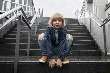 Portrait of blond boy crouching on stairs outdoors - EYAF00923