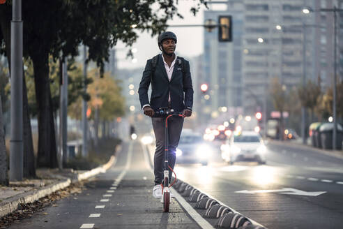 Portrait of businessman riding push scooter on bicycle lane in the evening - JSRF00801
