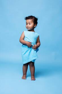 Portrait of barefoot little girl wearing light blue dress standing against blue background - DAWF01263