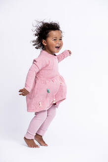 Portrait of barefoot little girl dressed in pink hopping in front of white background - DAWF01269