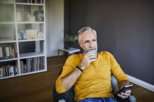 Relaxed mature man at home with cell phone and cup of coffee - FMKF06105
