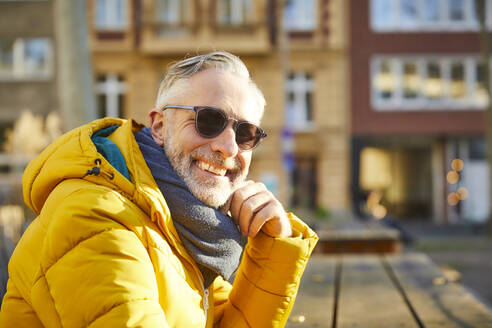 Portrait of smiling mature man wearing sunglasses in the city - FMKF06114
