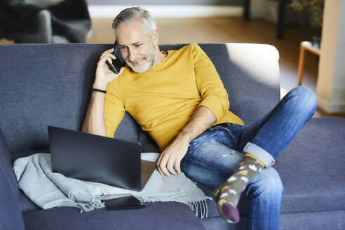 Mature man using cell phone and laptop on couch at home - FMKF06120