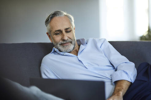 Mature man using laptop on sofa at home - FMKF06129