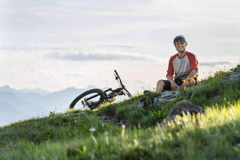 Mountainbiker in the evening light in Grisons, Switzerland - HBIF00010