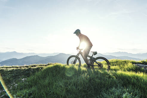 Mountainbiker against the sun on a way in Grisons, Switzerland - HBIF00013