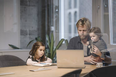 Casual businessman with two daughters working at desk in office - KNSF07442