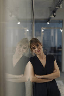 Portrait of businesswoman leaning against glass pane in office - KNSF07508