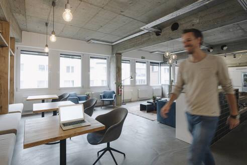 Casual businessman walking in modern office - KNSF07526