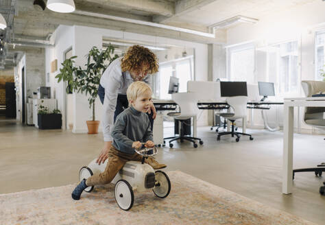 Businessman pushing son on toy car in office - KNSF07535