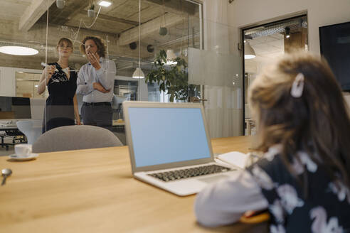 Businessman and businesswoman working on a project in office with girl using laptop in foreground - KNSF07550