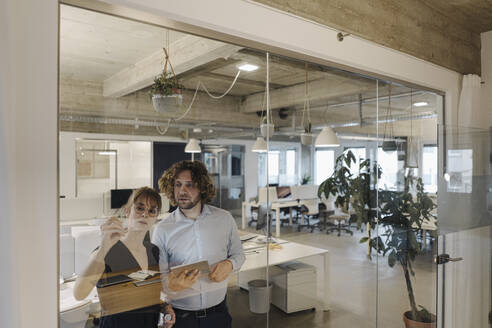 Businessman and businesswoman working on a project in office - KNSF07553