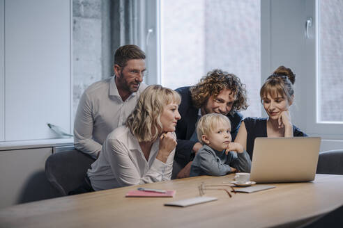 Business team with boy looking at laptop in office - KNSF07574