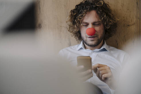 Businessman with red clown nose using cell phone in office - KNSF07592