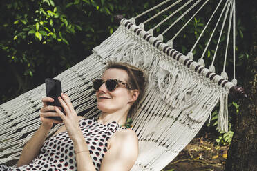 Smiling woman lying in a hammock using cell phone - CHPF00602
