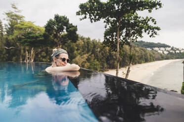 Woman relaxing in infinity pool, Nai Thon Beach, Phuket, Thailand - CHPF00617