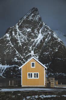 Norway, Moskenes, Lofoten Islands, Sakrisoy, Traditional Rorbu fishing cabin with Olstinden peak in background - JRAF00017