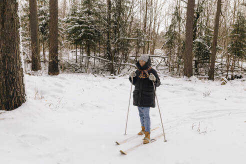Smiling woman on skis in winter forest - KNTF04179