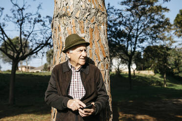 Old man using smartphone, leaning on tree trunk - JRFF04107