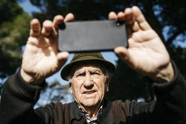 Old man taking pictutes with his smartphone - JRFF04110