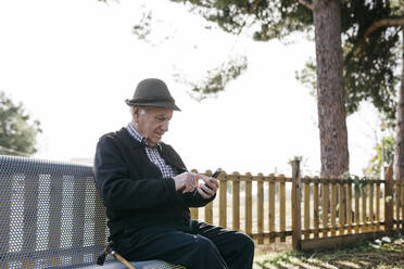 Old man with, sitting on bench, using smartphone - JRFF04113