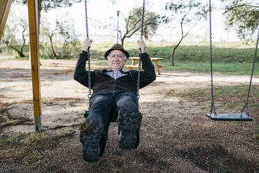 Old man swinging on playground in park - JRFF04116