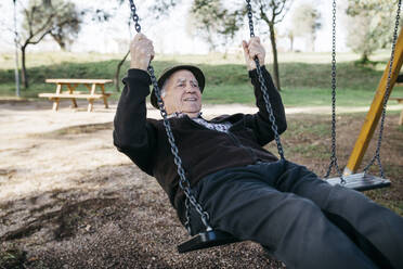 Old man swinging on playground in park - JRFF04119