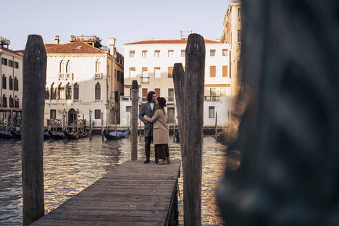 Young couple on a jetty at the Canal Grande in Venice, Italy - MAUF03292