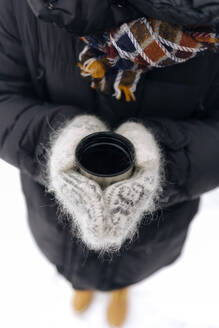 Woman's hands holding thermo mug outdoors - KNTF04199