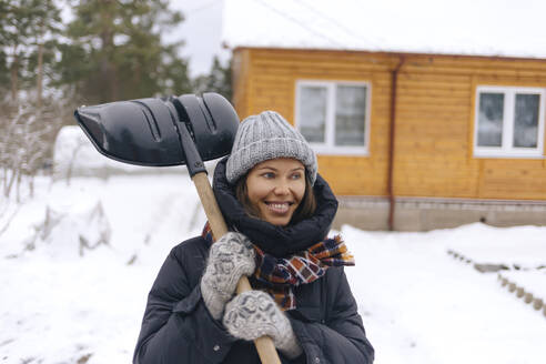 Portrait of smiling woman with snow shovel - KNTF04205