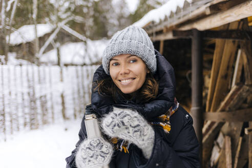 Portrait of happy woman with thermo flask in winter - KNTF04214