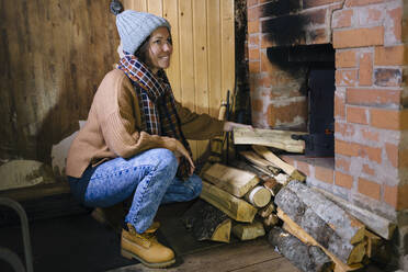 Smiling woman near the fireplace at home - KNTF04217