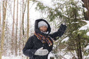 Portrait of laughing woman in winter forest enjoying snowfall - KNTF04219