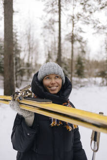 Portrait of smiling woman with skis in winter forest - KNTF04222