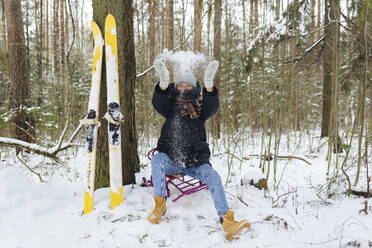Woman with skis sitting on sledge in winter forest throwing snow into the air - KNTF04228