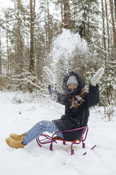 Happy woman sitting on sledge throwing snow into the air in winter forest - KNTF04231