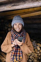 Young woman near a woodpile using smartphone - KNTF04236