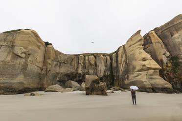 New Zealand, Oceania, South Island, Otago, Dunedin, Woman with umbrella near cliffs on Tunnel Beach - FOF11800
