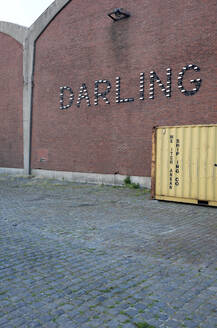 Belgium, Antwerp, Darling neon sign on warehouse wall - GISF00512