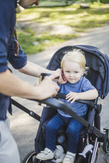 Midsection of man touching son sitting on baby carriage at public park - MASF16368