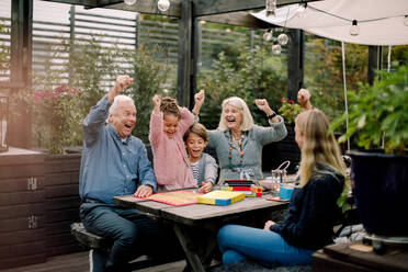 Cheerful family playing board game while sitting at table in backyard - MASF16461
