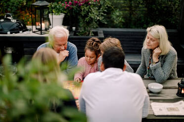Multi-generation family playing board game on table while sitting in patio - MASF16464