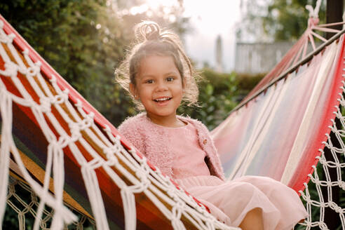 Portrait of smiling girl sitting in hammock at backyard - MASF16494