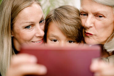 Close-up of multi-generation family taking selfie in mobile phone - MASF16500