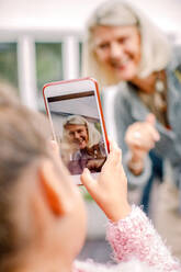 Granddaughter taking photograph of grandmother in mobile phone - MASF16503